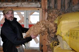Rune Thoresen viser frem gammel isolasjon fra et hus under renovering.